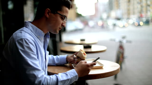 Businessman eating breakfast in sidewalk cafe and using phone