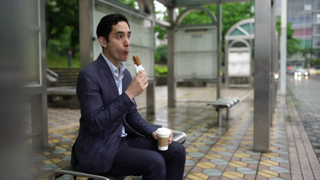 businessman eating breakfast while waiting for a bus - cream cake stock videos & royalty-free footage