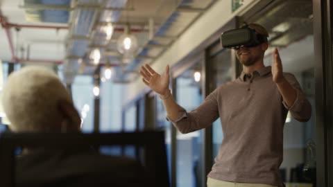 vídeos y material grabado en eventos de stock de empresario disfrutando de la tecnología moderna en la oficina - simulador de realidad virtual