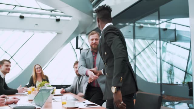 businessman entering an office and shaking hands - handshake stock videos & royalty-free footage