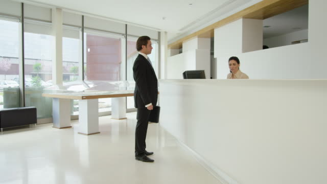 businessman entering reception area of modern office building, taking to receptionist, then being greeted by other businessman who enters the frame