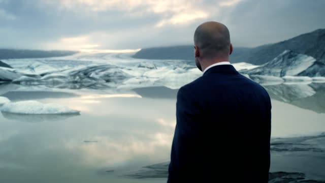 businessman escaping from work. glacier lagoon with dramatic sky - suit stock videos & royalty-free footage