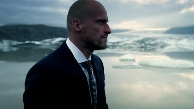 businessman escaping from work. glacier lagoon with dramatic sky - white collar worker stock videos & royalty-free footage