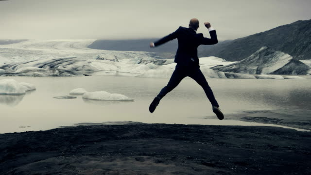 businessman escaping from work. joy on glacier lagoon with dramatic sky - businessman stock videos & royalty-free footage