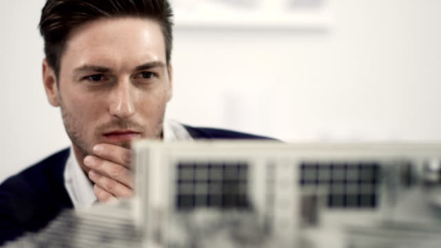 Businessman examine architecture model