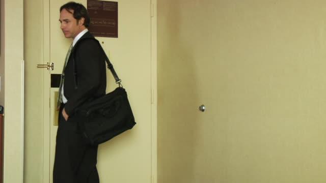 ms, businessman exiting hotel room - dreiviertelansicht stock-videos und b-roll-filmmaterial