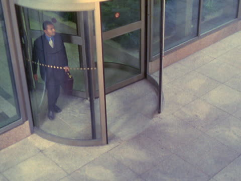 businessman exiting revolving door, greeting businesswoman - mpeg videoformat stock-videos und b-roll-filmmaterial