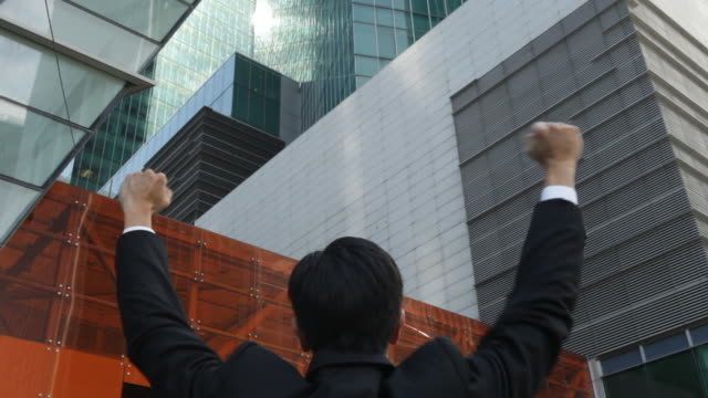 a businessman faces office buildings and raises his fists in the air. - 25 29 years stock videos & royalty-free footage