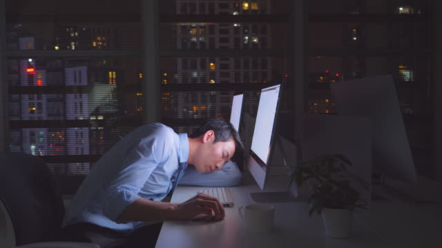 ms businessman falling asleep while working late at night, china - 残業点の映像素材/bロール