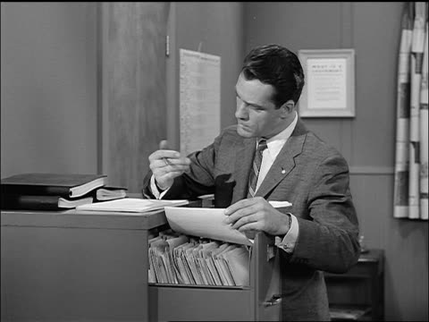 vidéos et rushes de b/w 1957 businessman (carl betz) finding file in cabinet in office + making notes - 1957