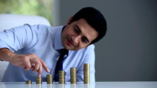businessman fingers climbing stack of coins, delhi, india - hemd und krawatte stock-videos und b-roll-filmmaterial
