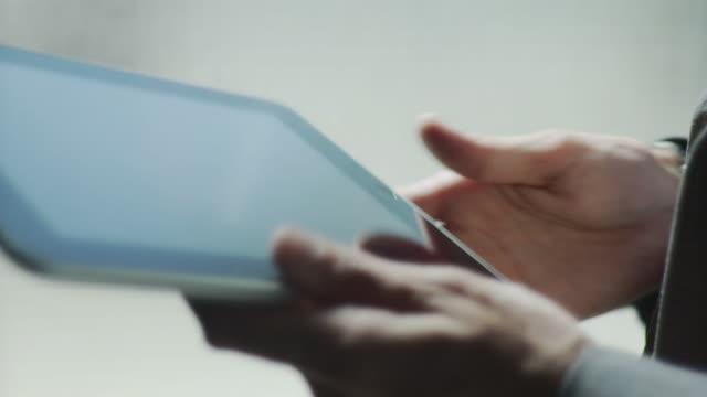 CU TU Businessman flipping through photos on digital tablet / Brooklyn, New York, USA