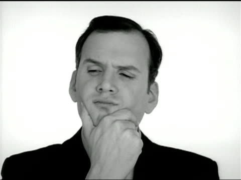 a businessman frowns as he holds his chin and then he shrugs and smiles. - frowning stock videos & royalty-free footage