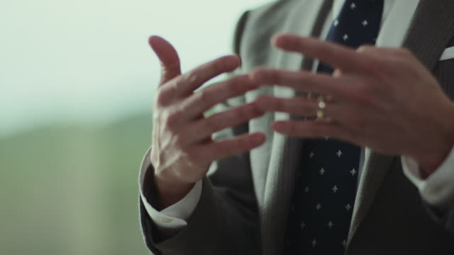 Businessman gestures with hands.
