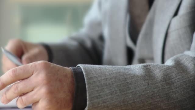 cu, selective focus, businessman gesturing at conference table, mid section, berlin, germany - hel kostym bildbanksvideor och videomaterial från bakom kulisserna