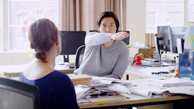 MS businessman gesturing during discussion with businesswoman in office