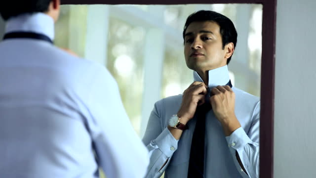 businessman getting dressed in front of mirror, delhi, india - shirt and tie stock-videos und b-roll-filmmaterial