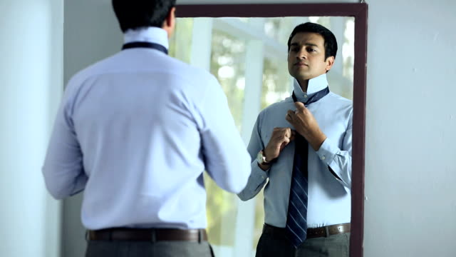 Businessman getting dressed in front of mirror, Delhi, India