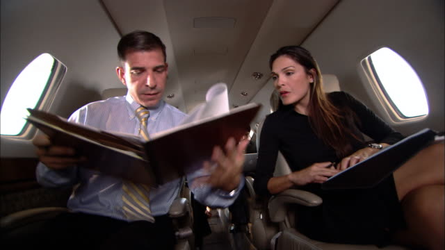 MS businessman giving businesswoman documents to sign on corporate jet