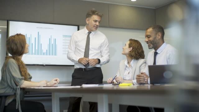 vidéos et rushes de homme d'affaires donnant la présentation dans la salle de conseil - diagramme en bâtons