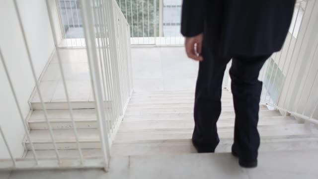 stockvideo's en b-roll-footage met businessman going downstairs - compleet pak
