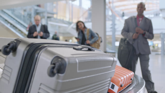 vídeos y material grabado en eventos de stock de businessman grabs checked luggage off conveyor belt in baggage claim. low angle. - equipaje