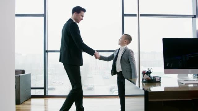 stockvideo's en b-roll-footage met zakenman groeten en schudden handen met jonge zakenman jongen, real-time - verantwoordelijkheid