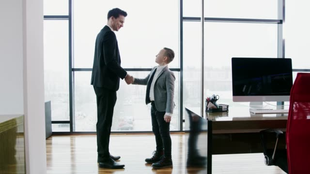 businessman greeting and shaking hands with young businessman boy, real time - selling stock videos & royalty-free footage