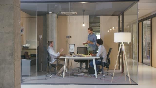 vídeos de stock e filmes b-roll de businessman greeting male professionals at office - vidro