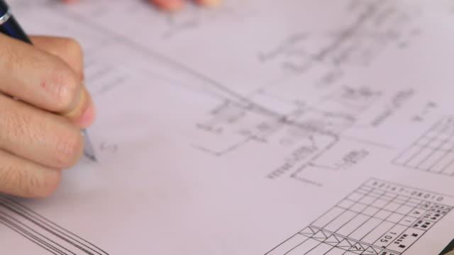 HD: Businessman hand checking construction blueprint