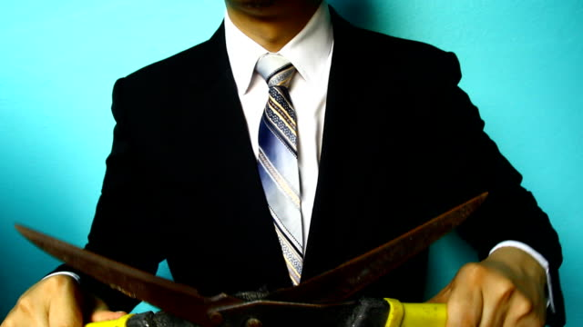 businessman hand with grass scissors - scissors stock videos and b-roll footage