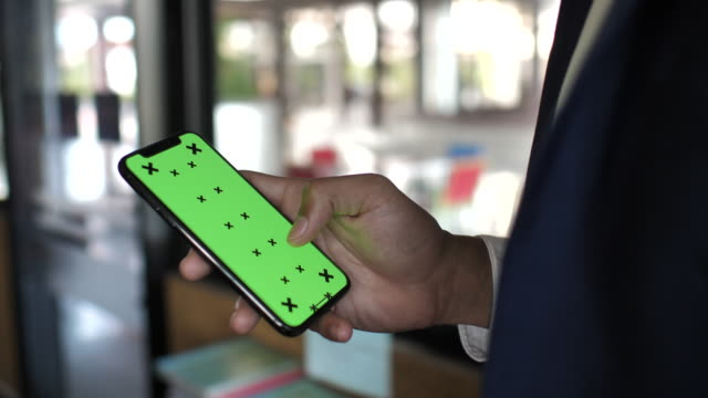 businessman hands hold smartphone with green screen display - template stock videos & royalty-free footage