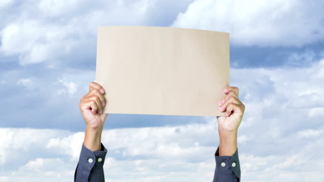 stockvideo's en b-roll-footage met businessman hands holding blank paper with clouds move background - bord bericht