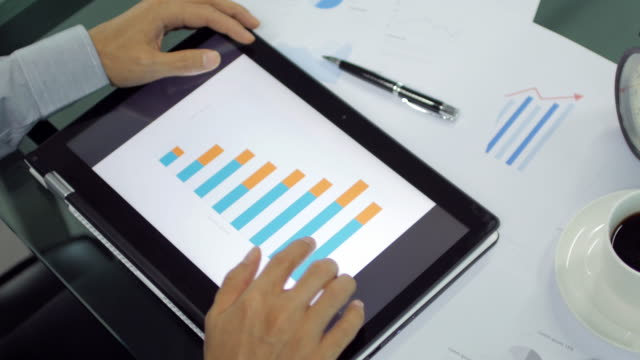 Businessman Hands touching on digital tablet for analyze graph , dolly shot left to right