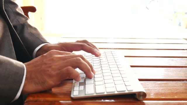 businessman hands typing on keyboard on wood table - e learning stock videos & royalty-free footage