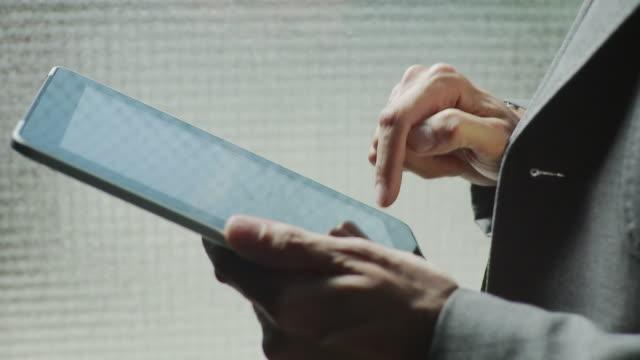 CU Businessman hands using tablet computer / Brooklyn, New York, USA