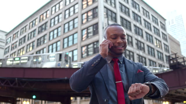 businessman having a conversation with mobile phone in downtown chicago - checking the time stock videos & royalty-free footage