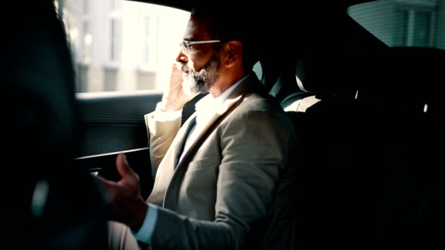 Businessman having a phone call in a car