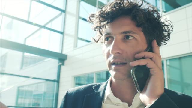vidéos et rushes de homme d'affaires ayant un appel téléphonique. - client