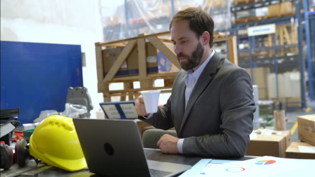 businessman having coffee and looking at laptop in warehouse - e mail video stock e b–roll