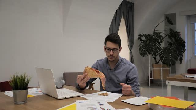 vidéos et rushes de homme d'affaires ayant des méfaits dans le bureau tout en mangeant la pizza - 18 23 mois