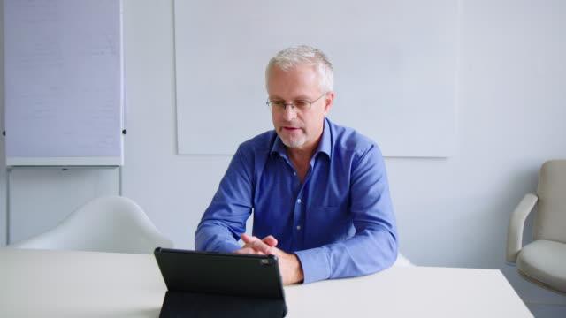 geschäftsmann mit videokonferenz über ein digitales tablet - tablet benutzen stock-videos und b-roll-filmmaterial