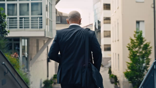 slo mo businessman heading to work - rear view stock videos & royalty-free footage