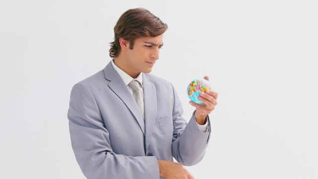 vídeos de stock e filmes b-roll de businessman holding a small globe - só um rapaz