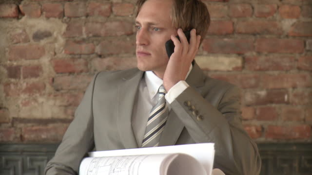 ms businessman holding blueprints and talking on phone, new york city, new york, usa - one mid adult man only stock videos & royalty-free footage
