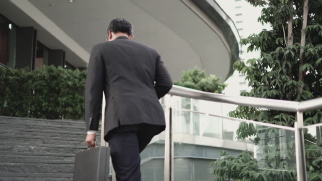 businessman holding briefcase and walking forward. - entering stock videos & royalty-free footage