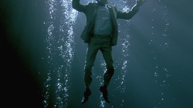 WS SLO MO Businessman holding briefcase sinking underwater / London, United Kingdom