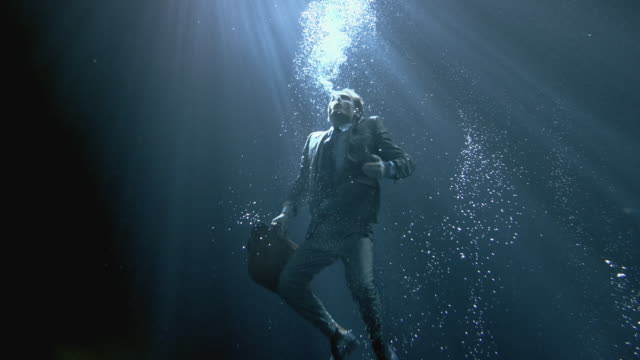 WS SLO MO Businessman holding briefcase swimming underwater / London, United Kingdom