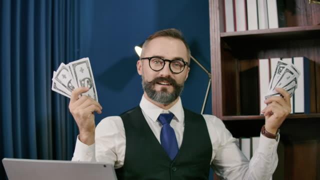 vidéos et rushes de homme d'affaires retenant des dollars d'argent comptant et regardant une caméra dans le bureau moderne. concept en ligne d'affaires - bouche des animaux