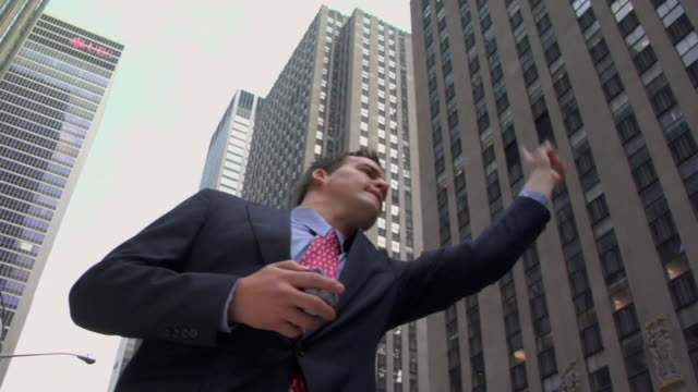 la ms businessman holding cell phone and hailing taxi cab near office buildings / new york, new york, usa - radio city music hall stock videos & royalty-free footage